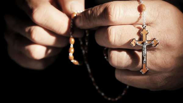stock-footage-praying-hands-with-rosary-cross-closeup1