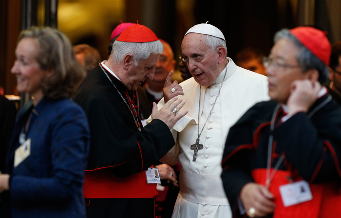 Pope Francis talks with Italian Cardinal Giuseppe Versaldi.