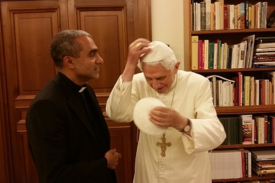 Msgr_Anthony_Figueiredo_exhanges_a_white_papal_zucchetto_with_Benedict_XVI_at_the_Vatican_on_Nov_6_2014_Photo_courtesy_of_Caritas_in_Veritate_International_CNA_11_12_14